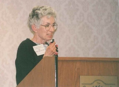 Lois Speaking at a Podium