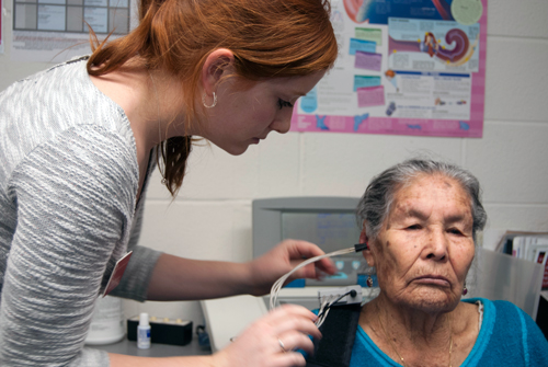 Audiology graduate student clinician performs immittance testing on an adult patient.