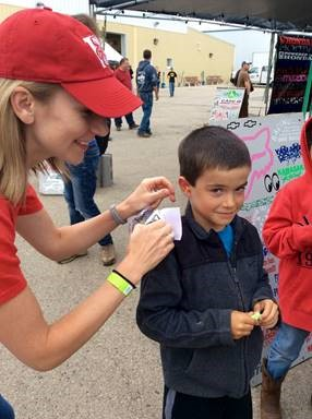 Dr. Melanie Buhr-Lawler, Audiologist at the UW Speech and Hearing Clinic, hands out earplugs at the tractor pull.