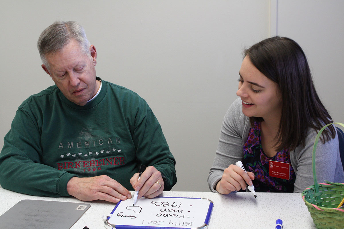 Student clinician working with a client on a handwriting exercise.