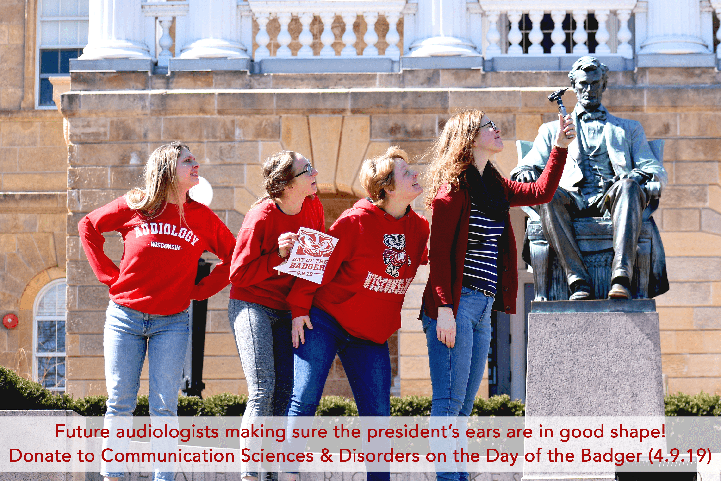 Audoliogy students posing with statue of Abraham Lincoln on Bascom Hill. Day of the Badger.